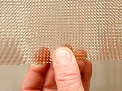 A piece of copper window screen is being held to show its details.