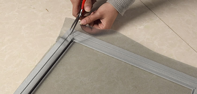 One is cutting the excess part of the screen, using a pair of scissors.