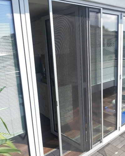 The picture shows a sliding door whose screen is pushed to be partially open to let people go in and out.