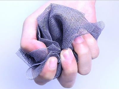 A piece of plastic window screen is held by a hand, while the gauze is soft enough to be folded.