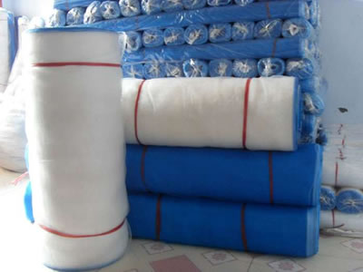 There are rolls of plastic window screen covered with PP bags.