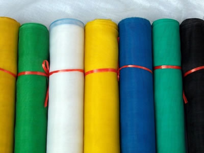 There are several rolls of plastic window screen in different colors.