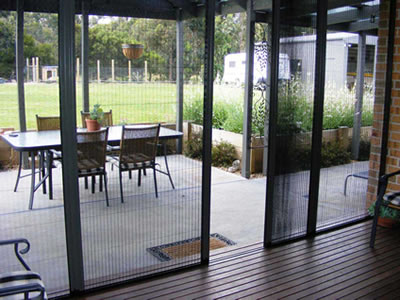There is a patio door with plated insect screen and through the screen, we still can see the courtyard clearly.