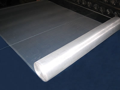 The picture shows a roll of aluminum alloy insect screen in silver white laid on a blue table.