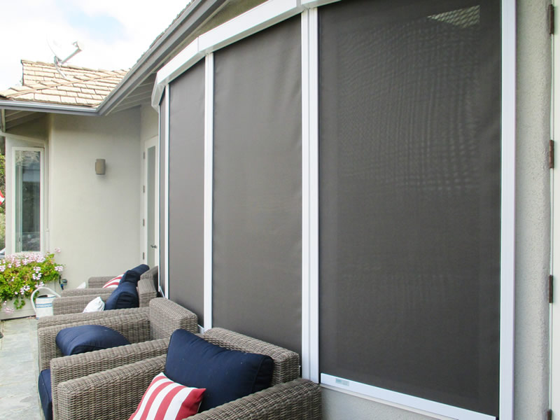 Three windows are covered with solar screen and four sofas in the yard.